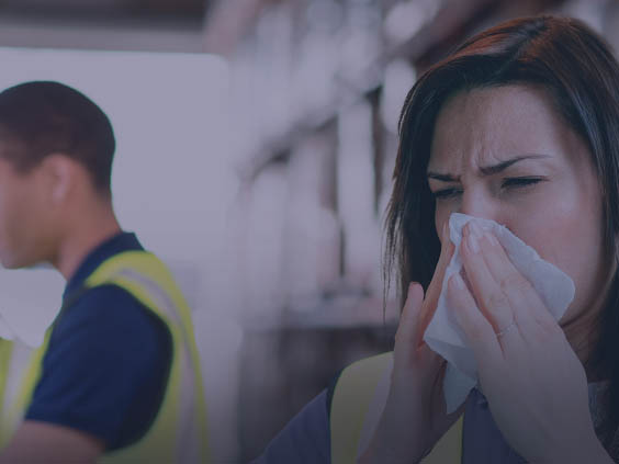 Worker blowing nose with co-worker nearby