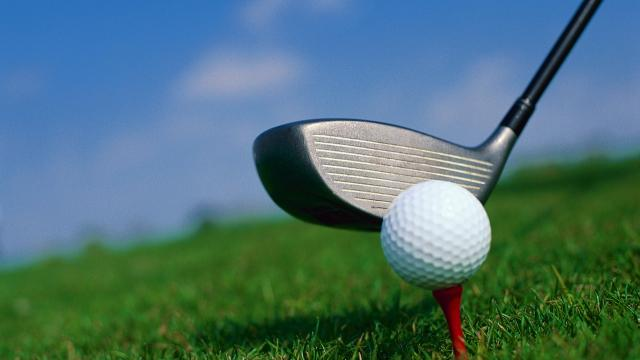 Golf ball on tee, with golf club lining up the shot