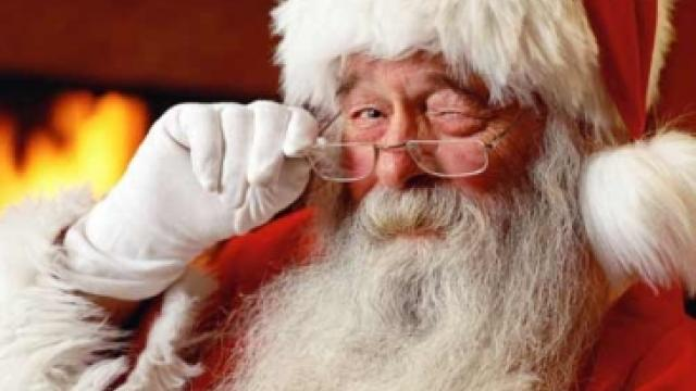 Santa adjusting his glasses in front of a roaring fire
